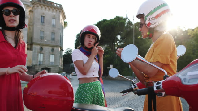 vintage scooter riding: girl friends with motorbikes in the center of rome - scooter stock videos & royalty-free footage