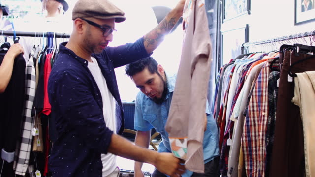 vidéos et rushes de propriétaire d'un magasin de vintage montrant la chemise au client - brocante