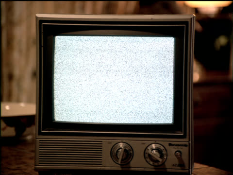 A vintage television set is turned on but the picture is just snow.