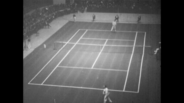 Vintage tennis action featuring two gentlemen playing a singles match watched by a large crowd at an indoor event circa 1925