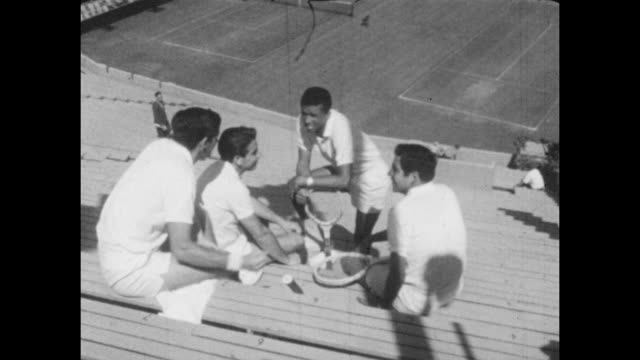 Vintage tennis featuring American Arthur Ashe Manuel Santana Roy Emerson and Rafael Osuna sitting and talking in a tennis stadium circa 1967