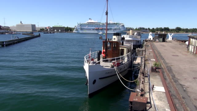 a vintage yacht is moored to a dock near a cruise ship. - bo tornvig stock videos & royalty-free footage
