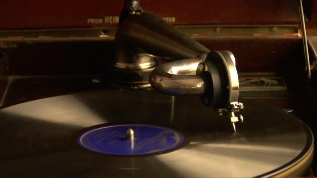vídeos de stock e filmes b-roll de cu, vinyl record spinning on antique record player - gira disco