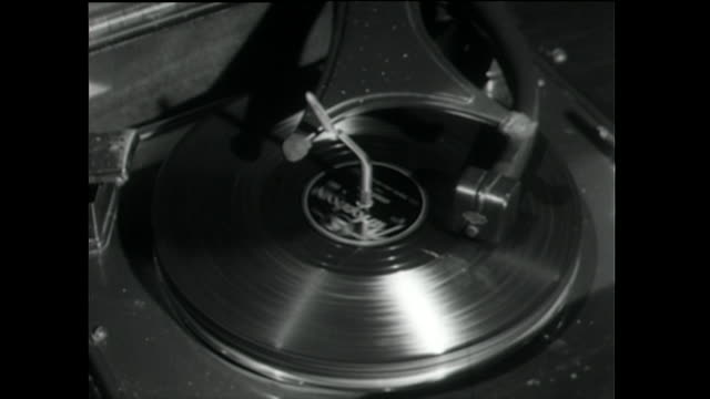 vinyl record spins and plays music on turntable; 1955 - 以前の点の映像素材/bロール