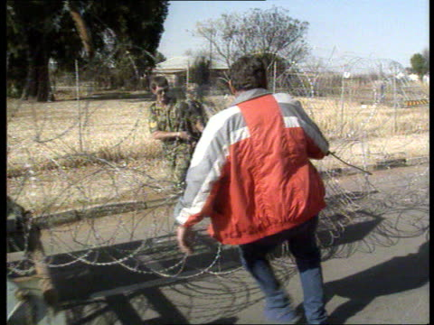 CONFLICT AWB violence 2200 SOUTH AFRICA Ventersdorp MS SIDE plain clothes policeman and soldier pulling coils of barbed wire along R MS Barbed wire...