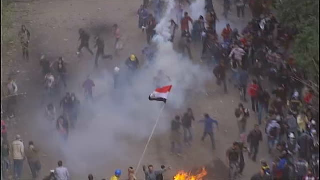 vídeos de stock, filmes e b-roll de violent clashes continue between the military and protesters egypt tahrir square ext high angle shot fire burning in street as crowd of egyptian... - arab spring