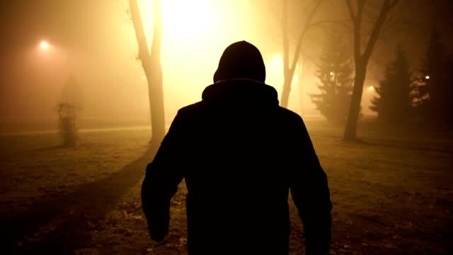 violent man walks at misty night. - hood clothing stock videos & royalty-free footage