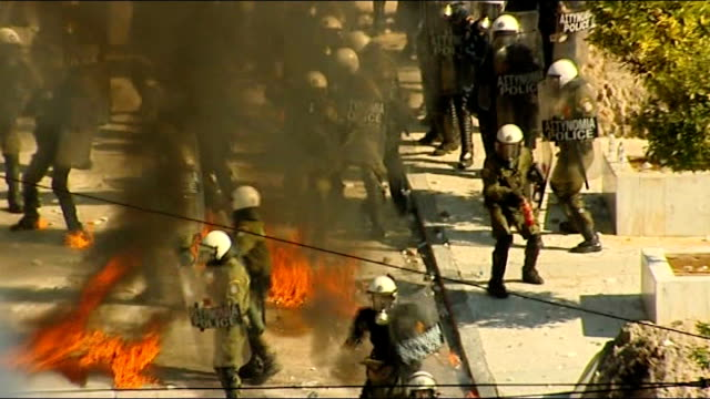 violent protests and stikes against government austerity measures greece athens ext high angle shots of riot police on street as petrol bombs land... - ユーロ圏債務危機点の映像素材/bロール