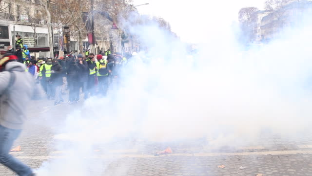 vidéos et rushes de violent protests on the iconic paris avenue champsélysées loud bangs can be heard as tear gas is fired at the yellow vests movement man holding... - confrontation