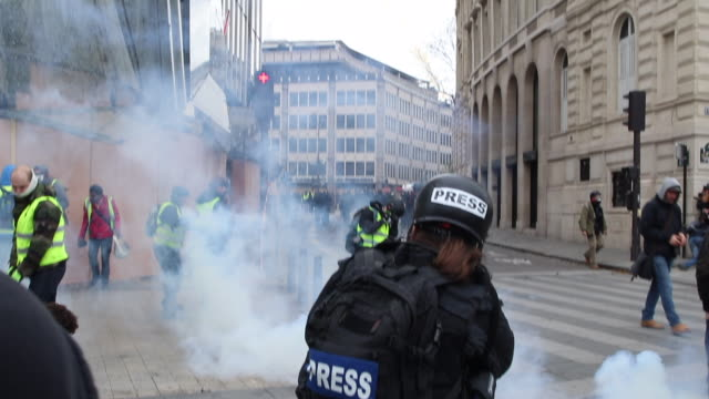 violent protests on the iconic paris avenue champsélysées loud bangs can be heard as tear gas is fired at the yellow vests movement man holding... - 対決点の映像素材/bロール