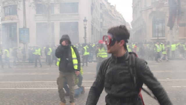 Violent protests on the iconic Paris avenue ChampsÉlysées Loud bangs can be heard as tear gas is fired at the yellow vests movement man holding...