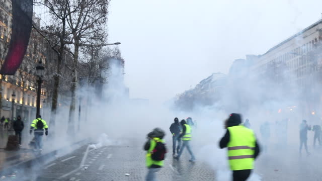 violent protests on the iconic paris avenue champsélysées tear gas is fired at the yellow vests movement demonstration of yellow vests on the avenue... - reflective clothing stock videos & royalty-free footage