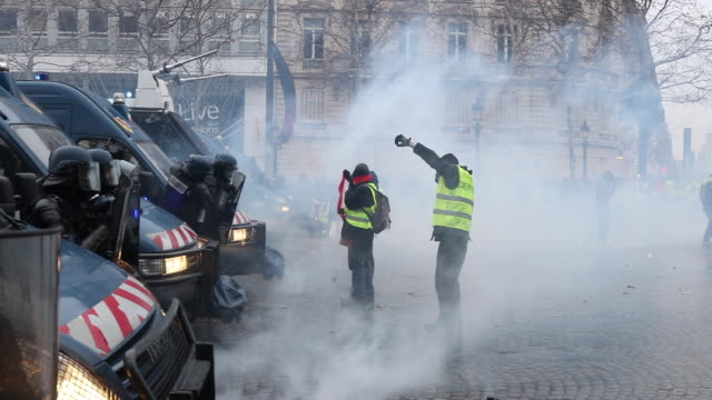 violent protests on the iconic paris avenue champsélysées tear gas is fired at the yellow vests movement demonstration of yellow vests on the avenue... - 対決点の映像素材/bロール