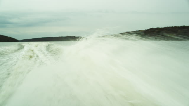 pov violet spray of water shooting from the rear of a speed boat racing across a lake creating a large wake. - wake water stock videos and b-roll footage