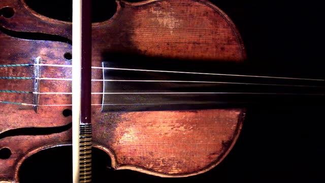 a violin bow draws across the strings of a violin. - violin stock videos & royalty-free footage