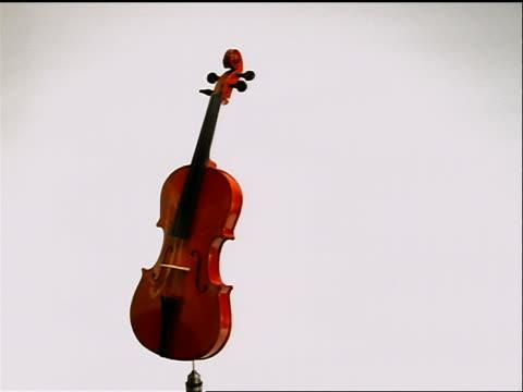 vídeos de stock, filmes e b-roll de violin rotating across white background - enfoque de objeto sobre a mesa