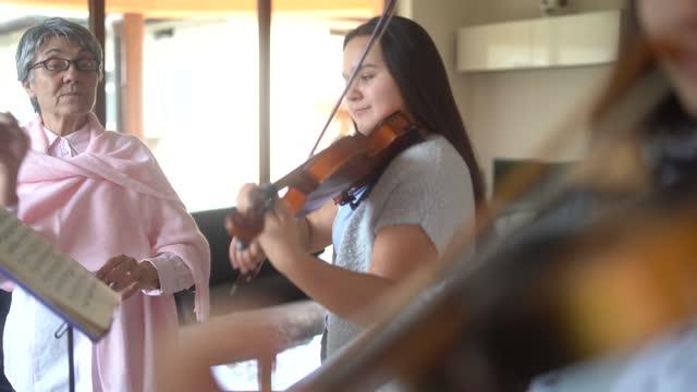 violin teacher teaching a high school girls to play violin - violinist stock videos & royalty-free footage