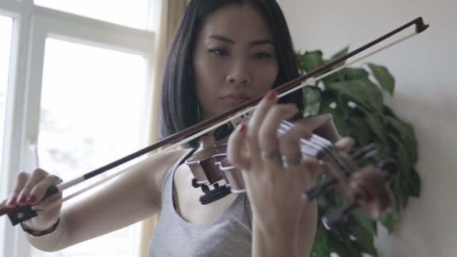 violinist asian woman playing violin at home - orchestra sinfonica video stock e b–roll