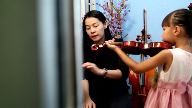 violinist playing violin musics with student