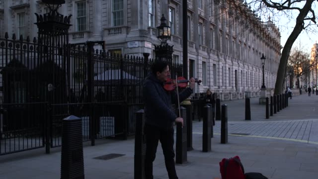 a violinist plays god save the queen and the star spangled banner outside downing street in a very quiet whitehall as the coronavirus crisis escalates - musician stock videos & royalty-free footage