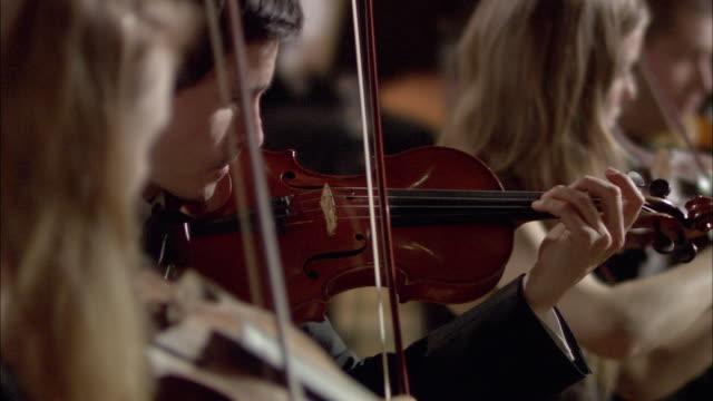 ms r/f pan violinists performing in orchestra / london, united kingdom - 30 34 ��r bildbanksvideor och videomaterial från bakom kulisserna