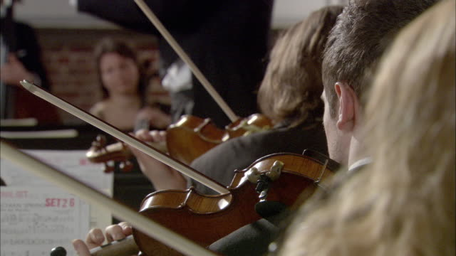 ms violinists playing in orchestra, conductor in background / london, united kingdom - conductor stock videos & royalty-free footage