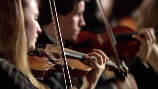 pan cu r/f violinists playing in orchestra / london, united kingdom - orchestra stock videos & royalty-free footage