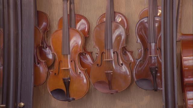 violins hang in a display case. - skåp med glasdörrar bildbanksvideor och videomaterial från bakom kulisserna