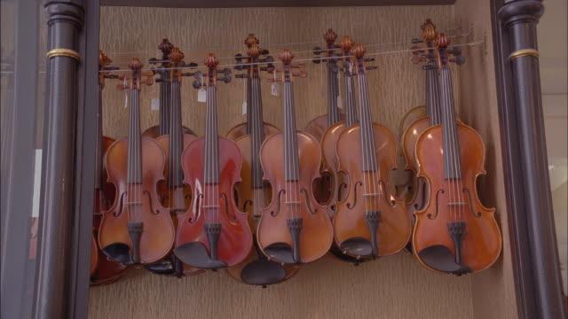 violins hang in a display case. - 陳列ケース点の映像素材/bロール