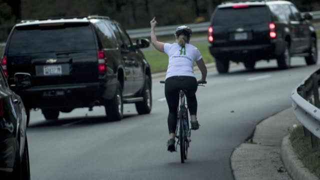 a viral afp photo taken in the fall of 2017 shows a cyclist flipping off donald trump's presidential convoy - convoy stock videos & royalty-free footage