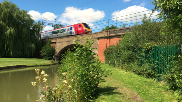 virgin diesel train passing over the grand union canal bridge. - railway bridge stock videos & royalty-free footage