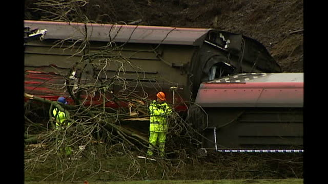 virgin train crashes in cumbria low angle shot of carriage lying pointing up at sky with accident investigators beside high angle shot of two... - lying on side stock videos & royalty-free footage