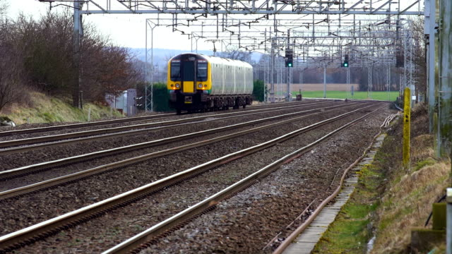 virgin/freight/arriva trains travel along the west coast main line at crewe, cheshire on february 7, 2018 in crewe, england. - 英チェシャー州点の映像素材/bロール