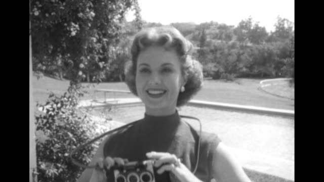 virginia mayo, standing in front of a swimming pool, holds camera with three lenses / she photographs john wayne and nancy olson at bottom left /... - loving cup stock videos & royalty-free footage