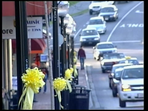 details emerge about gunman cho seunghui day blacksburg residents along in town past yellow ribbon rosettes attached to lampposts - itvイブニングニュース点の映像素材/bロール