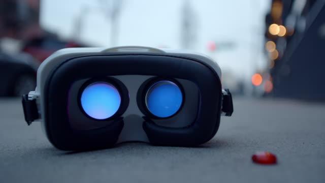 vidéos et rushes de lunettes de googles de casque de réalité virtuelle sur trottoir clignotant arrière - casque audio
