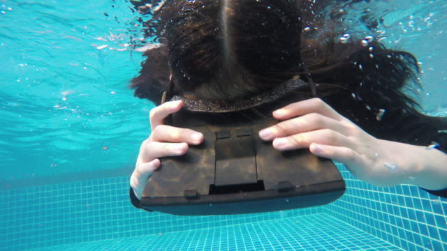 Virtual Reality Headset in Swimming pool under water by girl
