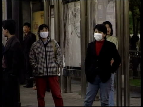 china outbreak/quarantine calls; itn government official speaking at press conference ext people along on street wearing face masks - 重症急性呼吸器症候群点の映像素材/bロール