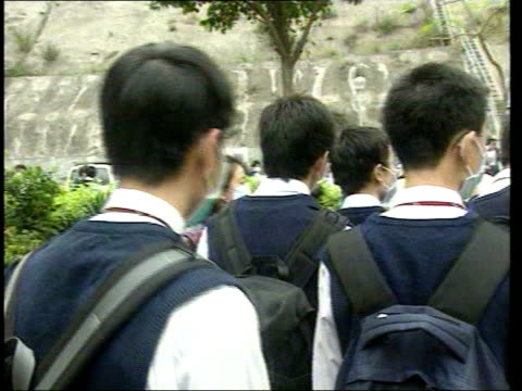 china outbreak/quarantine calls; itn hong kong: ext school children in school yard wearing face masks pupils given temperature checks by staff - 重症急性呼吸器症候群点の映像素材/bロール