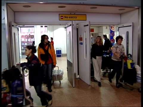 compulsory tests recommended for plane passengers; itn england: london: heathrow airport: passengers towards through arrivals hall as returning from... - 重症急性呼吸器症候群点の映像素材/bロール