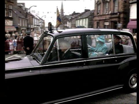 visit to lockerbie; scotland: lockerbie hm queen along holding flowers as escorted by uniformed men duke of edinburgh as chatting crowd in street... - betty thomas stock videos & royalty-free footage