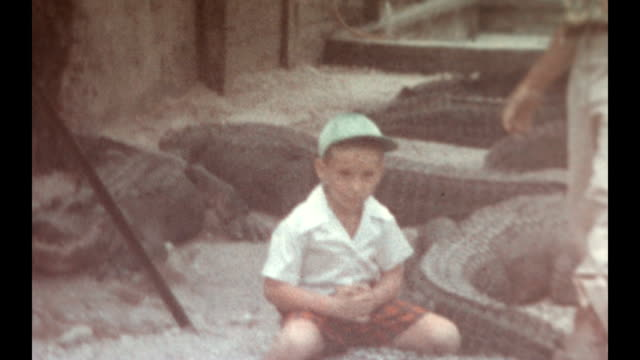 A visit to the Ross Allen's Reptile Institute / young boy sits on an alligator and wanders around.