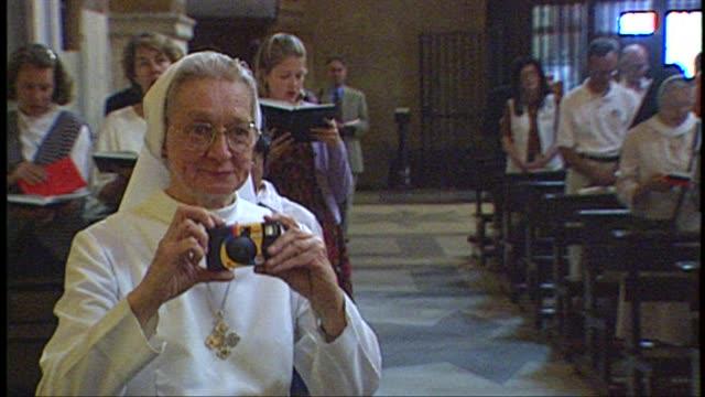 vídeos de stock, filmes e b-roll de a visiting chicago nun snaps a photo at the church of saint susanna at the baths of diocletian on june 29 1997 in rome italy - nun