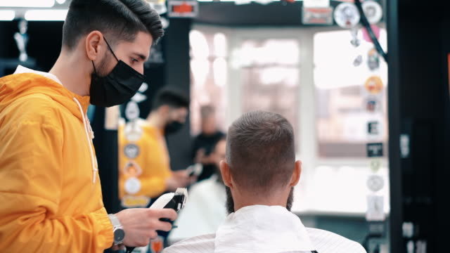 visiting the barber shop during covid-19 - barber stock videos & royalty-free footage