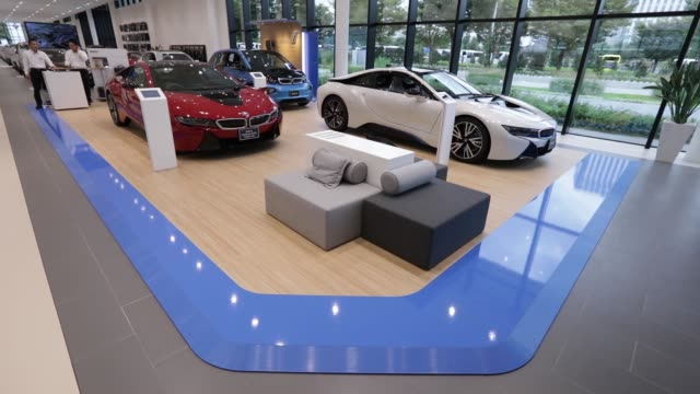 A visitor center inspects a BMW i3 electric vehicle manufactured by Bayerische Motoren Werke AG on display with an attendant left at the BMW Group...