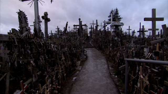 a visitor emerges onto a walkway of the hill of crosses. available in hd. - lithuania stock videos & royalty-free footage