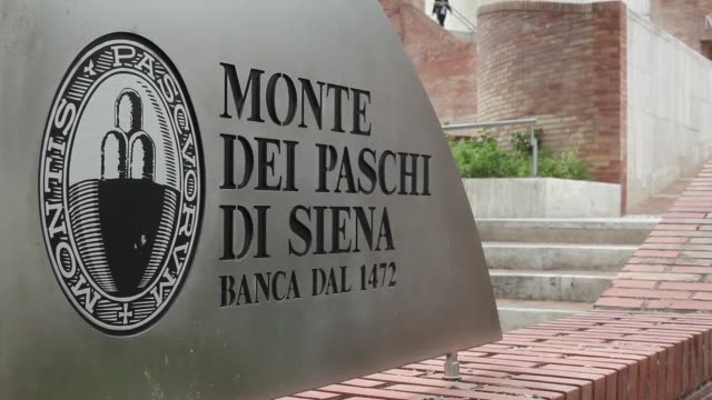 a visitor enters the administrative offices of banca monte dei paschi di siena spa in siena pedestrians leave the administrative offices of banca... - piazza del campo stock videos and b-roll footage