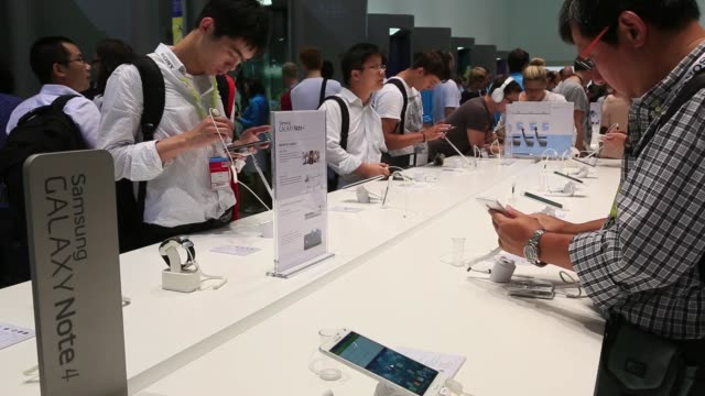 A visitor inspects a Samsung Galaxy Note 4 smartphone at the Samsung Electronics Co display stand at the IFA International Consumer Electronics Show...
