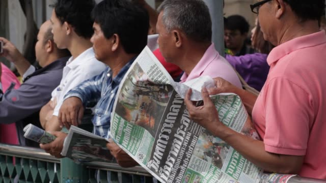 A visitor reads a newspaper near the blast site near the Erawan Hindu shrine in Bangkok Thailand on August 17th 2015 Shots Close up shot of the front...