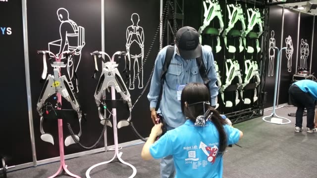 visitor tries a muscle suit in the tokyo university of science booth at japan robot week 2014 in tokyo, japan, on wednesday, oct 15 a robot arm,... - assistive technology stock videos & royalty-free footage